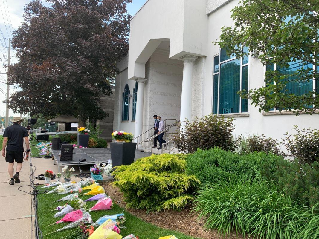 Des bouquets de fleurs sont disposés de chaque côté de l'entrée principale de l'édifice.