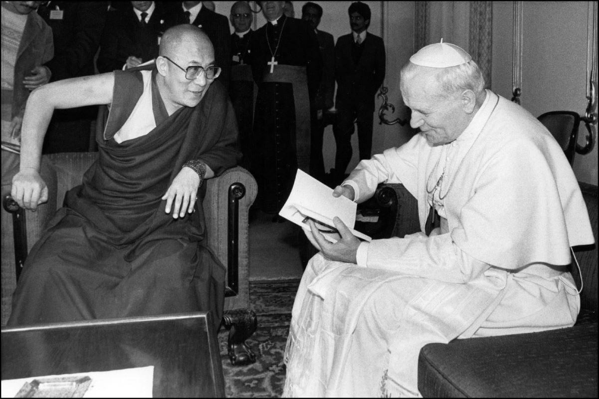 (2 février 1986) Durant sa visite en Inde, le pape Jean-Paul II tient dans ses mains un livre écrit par le 14e dalaï-lama.
