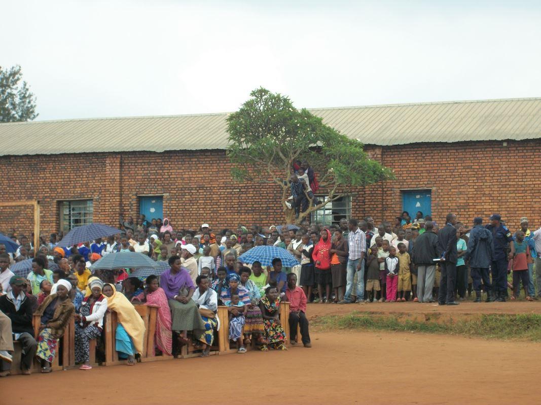 La communauté est rassemblée dans la cour de l'école pour entendre les discours sur l'unité et le renouveau, dont celui d'un rescapé et d'un participant au génocide.