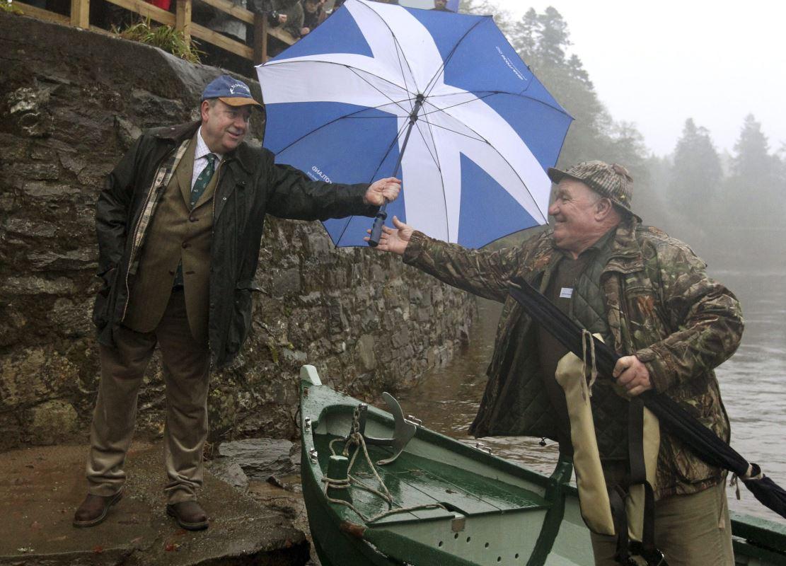 Le premier ministre d'Écosse Alex Salmond, à gauche, tend un parapluie à un pêcheur.