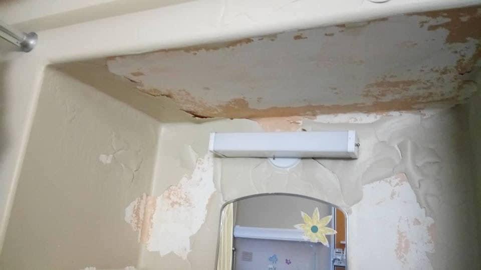 Une salle d'eau délabrée, dont la peinture tombe des murs