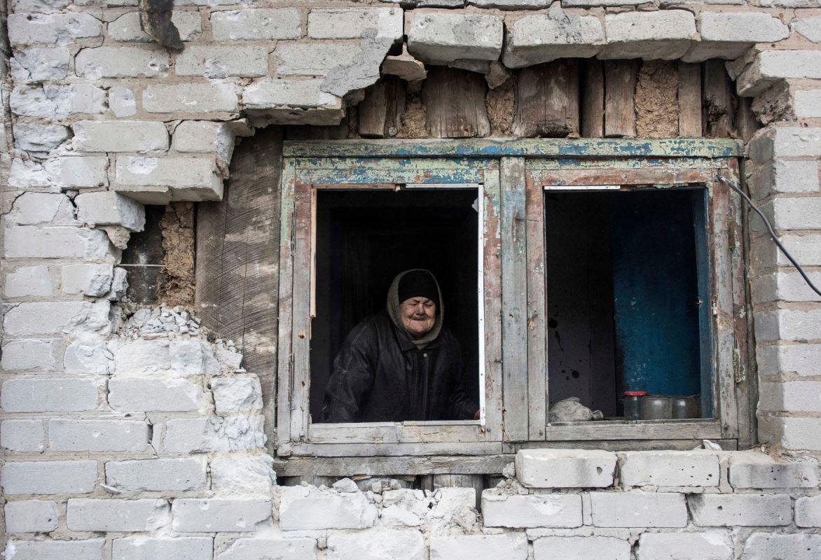 Une femme regarde par la fenêtre de sa maison, lourdement endommagée par les bombardements, à Avdiïvka, le 2 février 2017