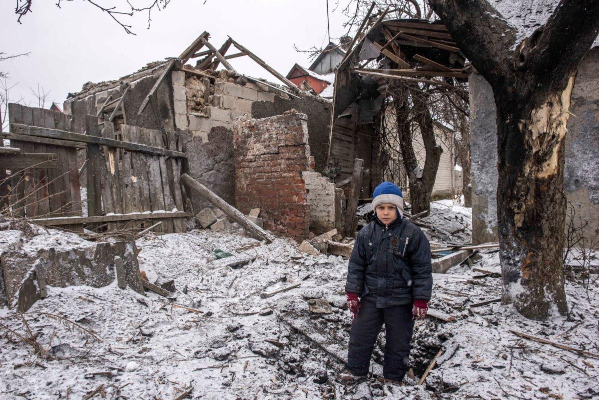 Un jeune garçon de huit ans pose devant ce qu'il reste de sa maison, lourdement endommagée par les bombardements, à Avdiïvka, le 2 février 2017