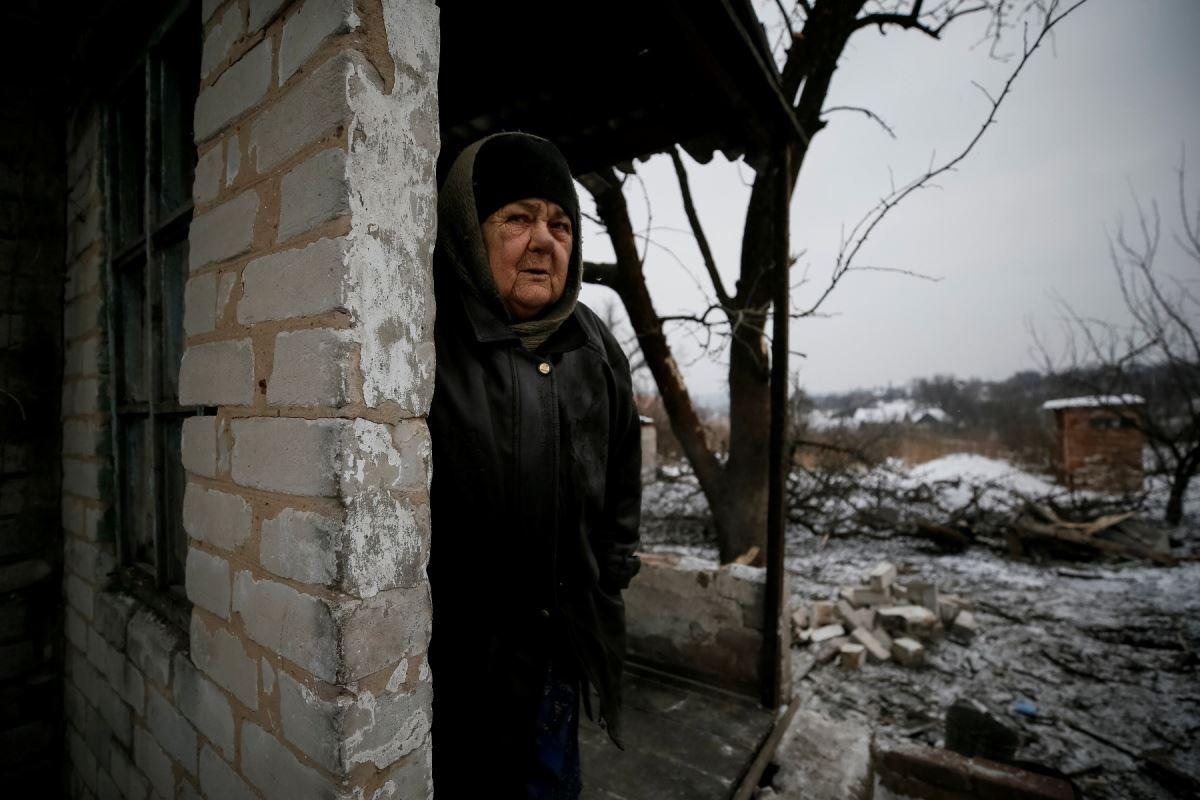 Une femme pose devant ce qu'il reste de sa maison, lourdement endommagée par les bombardements, à Avdiïvka, le 2 février 2017