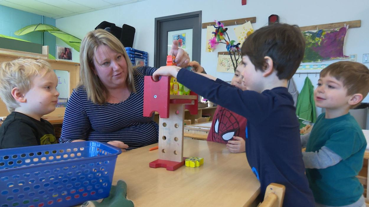 La directrice de la garderie éducative de Kingston, Nicole Keough joue avec des enfants ssur une table dans une salle de classe.