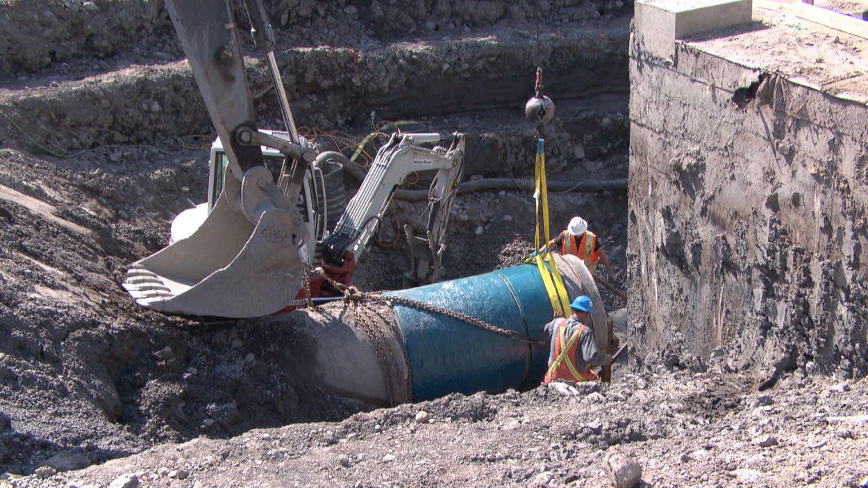 Des travailleurs déplacent un énorme tuyau à l'aide d'une grue.