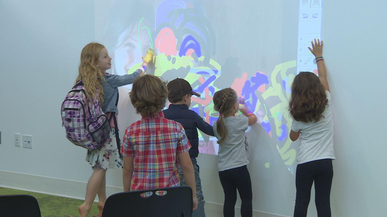 Des enfants écrivent sur un mur