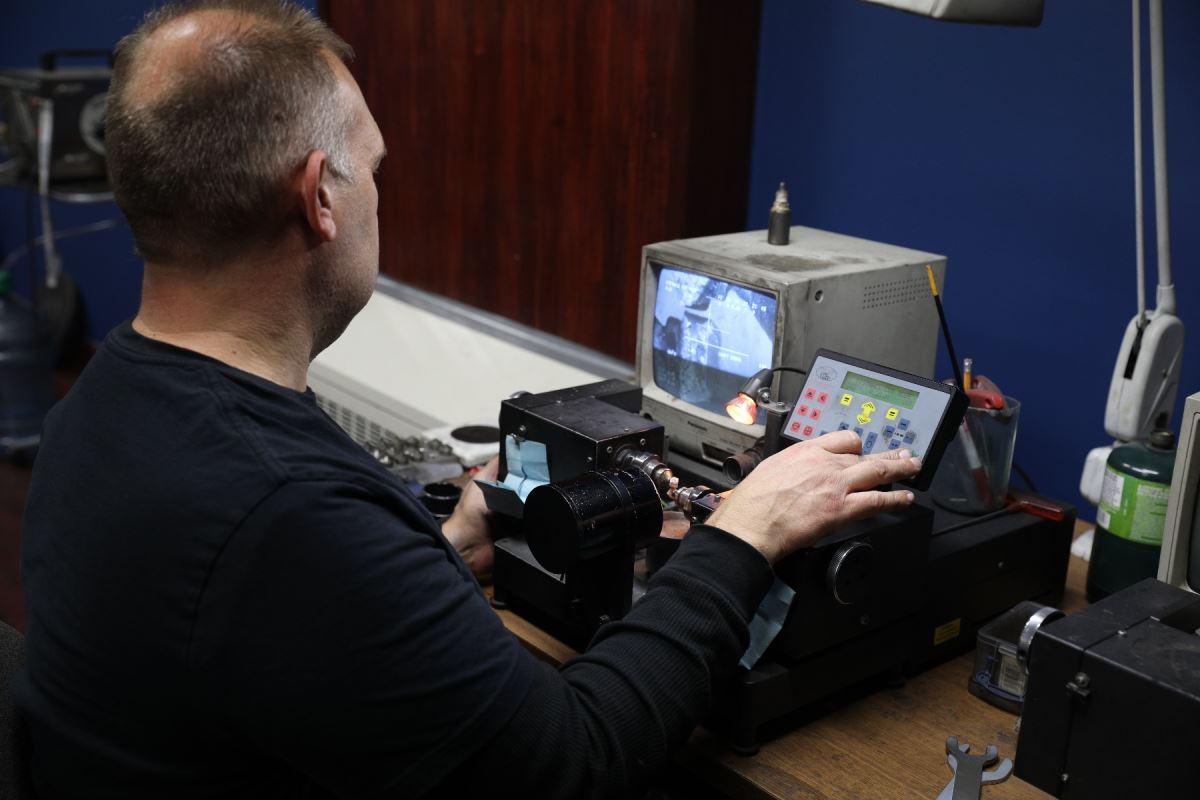 Un homme se tient devant un ordinateur et un diamant se fait bruter.