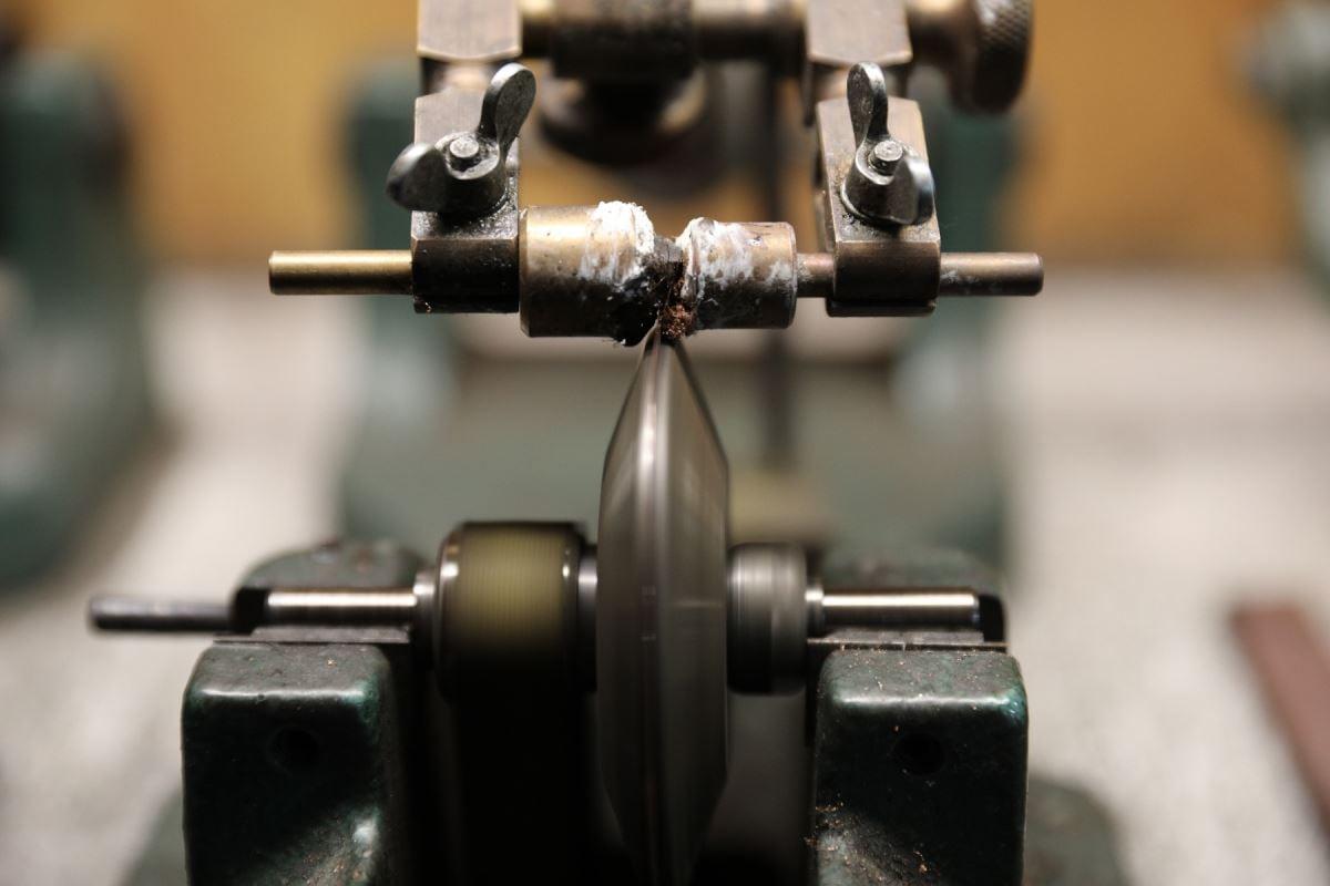Un diamant est tenu par un pince et un disque composé de cuivre est utilisé pour couper le diamant.