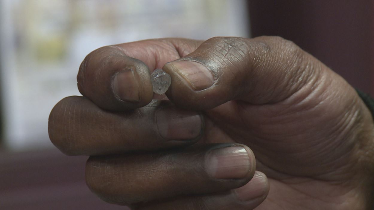 Une main tient un diamant à son état brut.