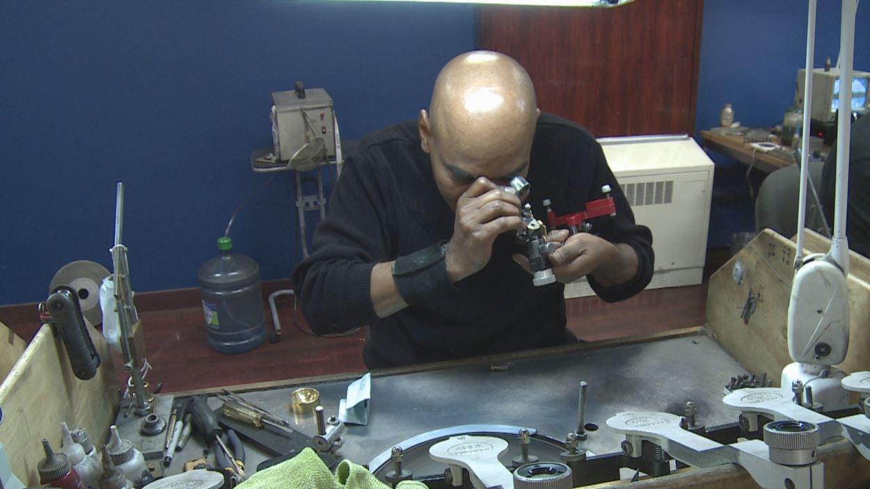 Un homme examine un diamant à la loupe.